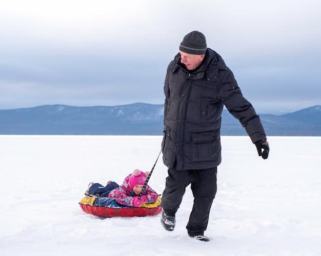 Een man, een senior, draagt een gelukkig meisje op een opblaasbare slee, slangen door de witte sneeuw.