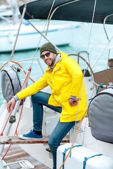 Een man een zeiler of een zeeman op de pier staat in de buurt van een zeeschip