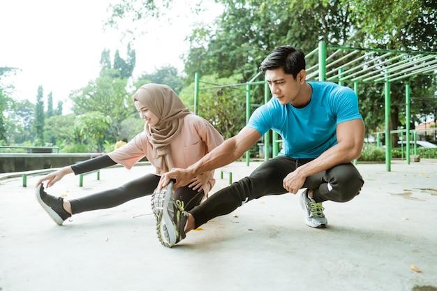 Een man en een gesluierd meisje in sportkleding voeren beenstrekkingen uit voordat ze gaan trainen in het park