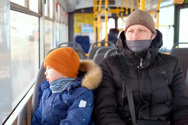 Een man en een jongen in een bus die medische maskers dragen. vader en zoon in een busrit met het openbaar vervoer tijdens covid