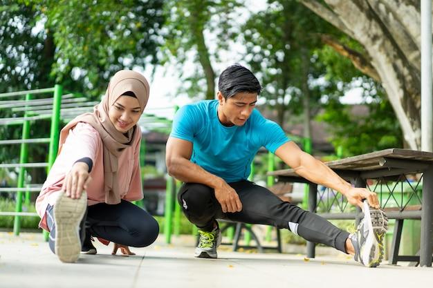 Een man en een meisje in een sluier in gymkleding doen samen de beenopwarmbeweging voordat ze in het park gaan trainen