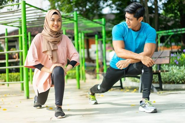 Een man en een meisje in een sluier in gymkleding lunges bewegingen doen tijdens het buiten samen trainen in het park