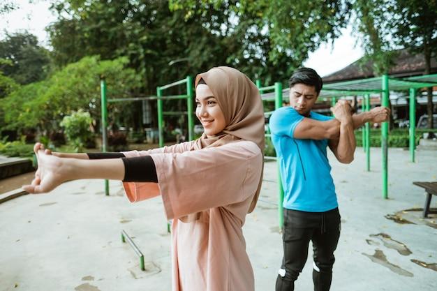 Een man en een meisje in een sluier in sportkleding voeren handstrekkingen samen uit in het park