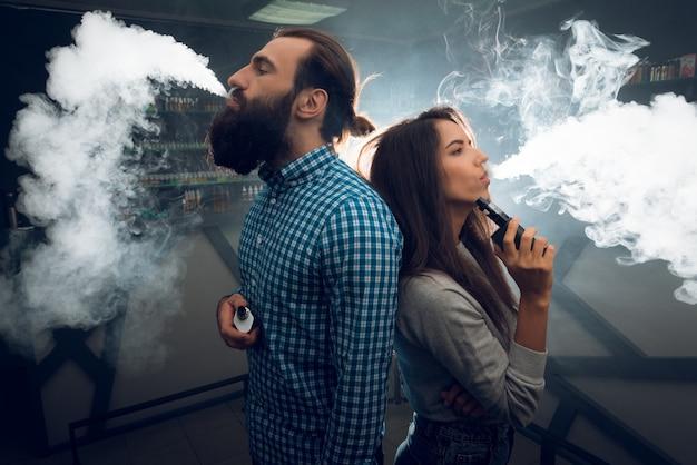 Een man en een meisje roken en ontspannen in een nachtclub.
