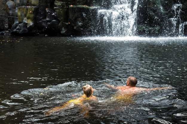 Een man en een meisje zwemmen in een waterval. mensen bij de grotwaterval. baden.