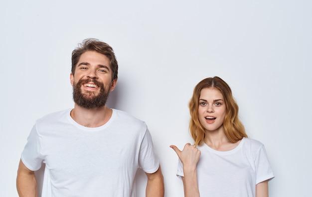 Een man en een mooie vrouw in dezelfde kleren aan een lamp gebaren met hun handenportret