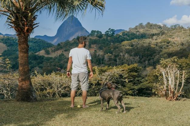 Een man en een pit bull-hond spelen en bewonderen de natuur en de bergen van petrã,polis, in rio de janeiro, brazilië. liefdevolle relatie tussen mens en dier.