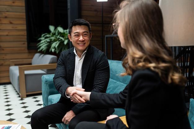 Een man en een vrouw beëindigen een zakelijke bijeenkomst en schudden elkaar de hand