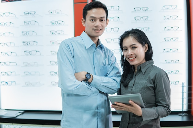 Een man en een vrouw brillen winkeleigenaar die een tablet vasthoudt terwijl hij tegen de muur van een glazen etalage vitrine in een opticien staat