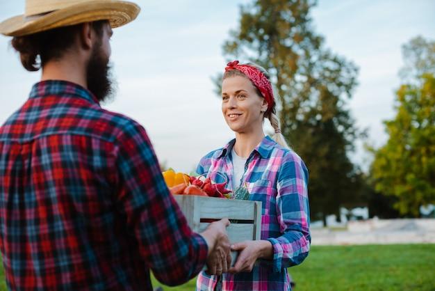 Een man en een vrouw die een doos met een oogst van boerderijgroenten van de tuin houden.