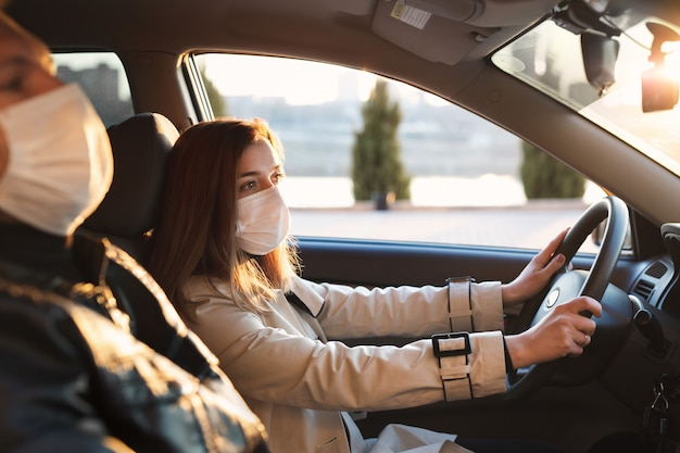 Een man en een vrouw dragen medische maskers en rubberen handschoenen om zichzelf te beschermen tegen bacteriën en virussen tijdens het autorijden. de vrouw achter het stuur. coronavirus (covid-19