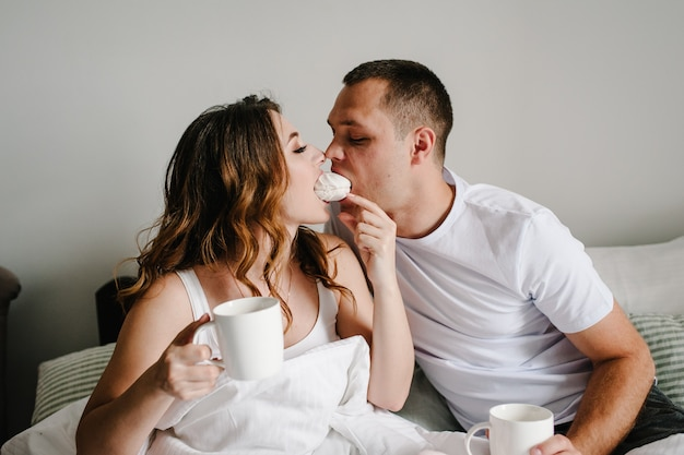 Een man en een vrouw drinken koffie en eten marshmallows in bed
