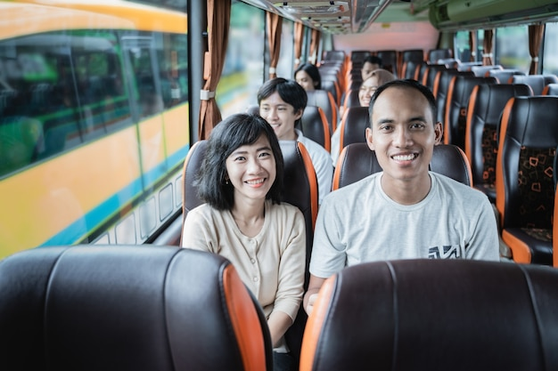 Een man en een vrouw glimlachen terwijl ze tijdens het reizen in de bus zitten