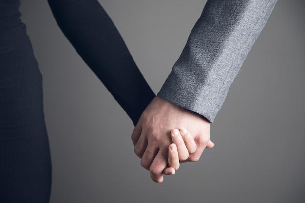 Een man en een vrouw houden elkaars hand vast