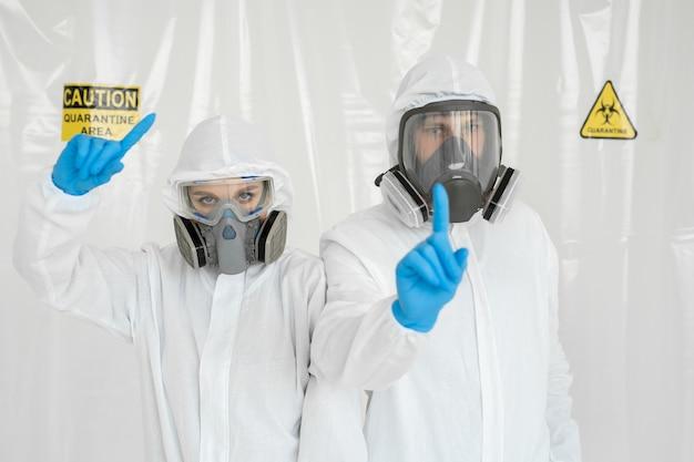 Een man en een vrouw in beschermende pakken en gasmaskers, die tijdens quarantaine hun hoofd vasthouden