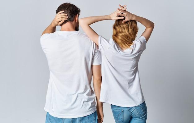 Een man en een vrouw in dezelfde t-shirts en spijkerbroek gebaren met hun handen, achteraanzicht
