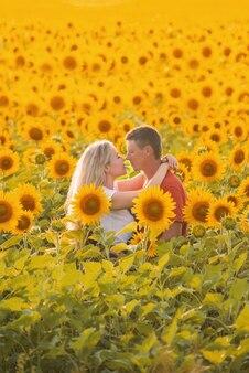 Een man en een vrouw in een veld met zonnebloemen kussen en lopen