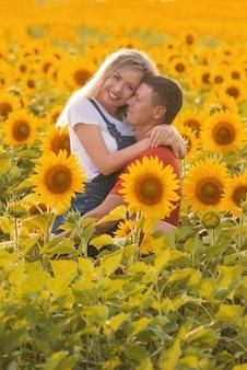 Een man en een vrouw in een veld met zonnebloemen