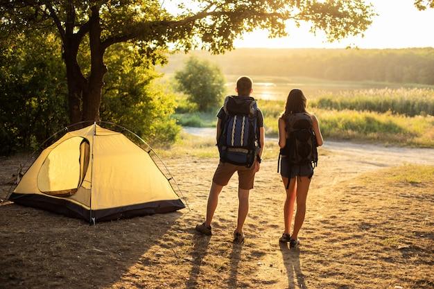 Een man en een vrouw in een wandeltocht met rugzakken in de buurt van een tent bij zonsondergang. huwelijksreis in de natuur