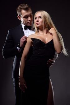 Een man en een vrouw in elegante outfits omhelzen elkaar hartstochtelijk en genieten van dit moment