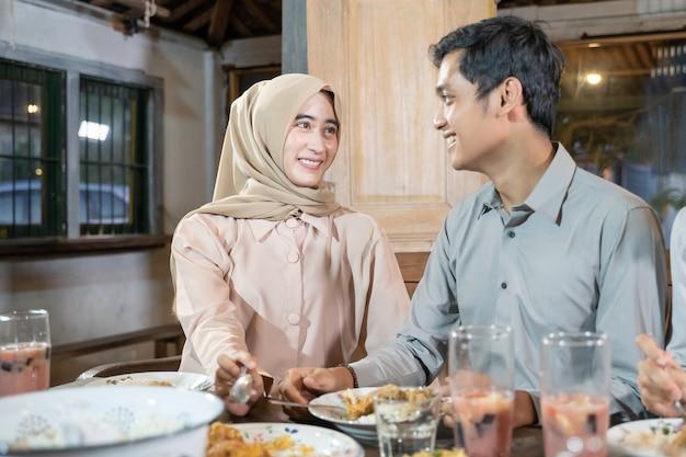 Een man en een vrouw in hijab staren elkaar aan terwijl ze samen bijgerechten eten tijdens iftar
