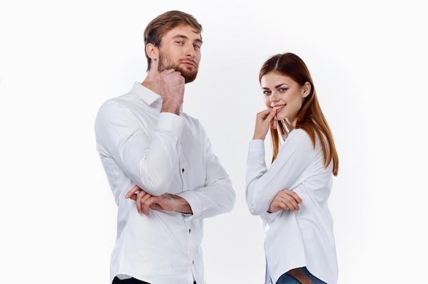 Een man en een vrouw in identieke hemden staan gebarend met hun handen op een lichte achtergrond