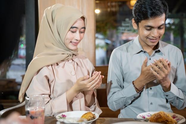 Een man en een vrouw in sluier bidden samen voor het eten