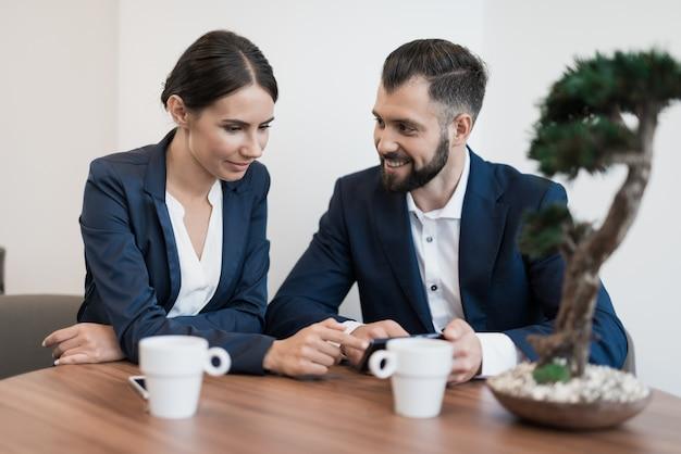 Een man en een vrouw in strakke pakken zijn aan het discussiëren.