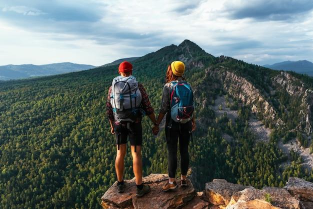 Een man en een vrouw in toeristische uitrusting staan op een rots en bewonderen het panoramische uitzicht. een verliefd stel op een rots bewondert de prachtige uitzichten. een verliefd stel is op reis. een stel op wandeling