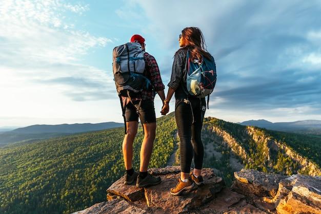 Een man en een vrouw in toeristische uitrusting staan op een rots en bewonderen het panoramische uitzicht. twee toeristen met rugzakken genieten van het uitzicht op de zonsondergang vanaf de top van de berg. backpacken reis