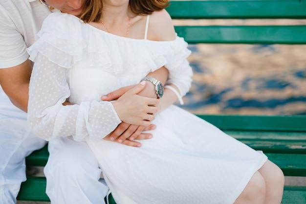 Een man en een vrouw in witte kleren zitten op een groene bank waar een man zachtjes een vrouw uit knuffelt