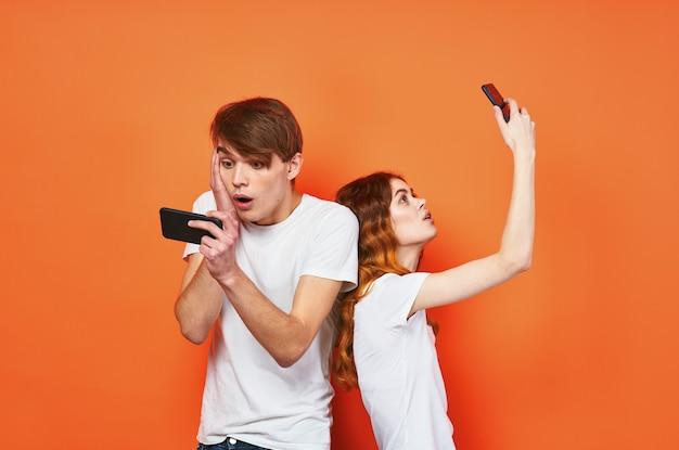 Een man en een vrouw in witte t-shirts met telefoons communicatie-entertainment