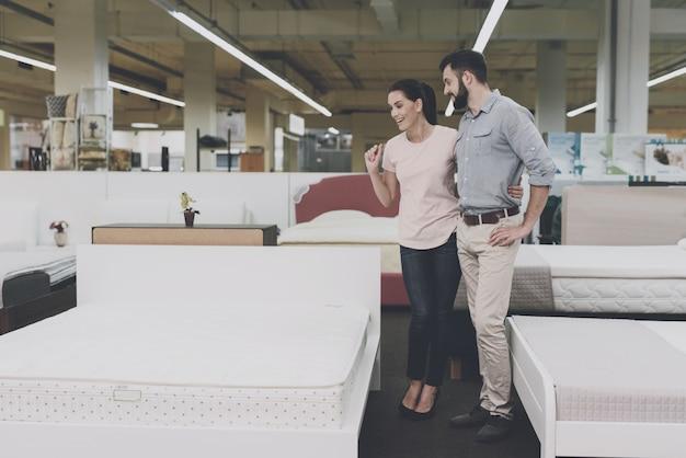 Een man en een vrouw kiezen een bed in de winkel.