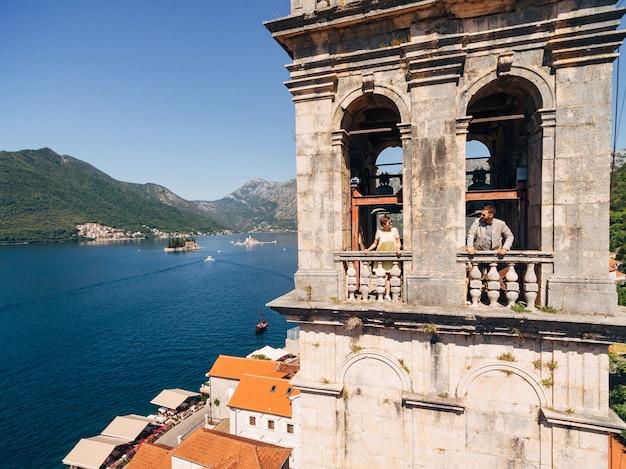 Een man en een vrouw kijken uit de ramen van de toren en kijken elkaar aan over het oude centrum van perast. hoge kwaliteit foto