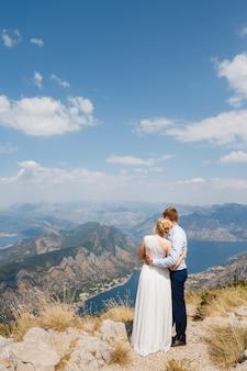 Een man en een vrouw knuffelen elkaar op de berg lovcen, een panoramisch uitzicht over de baai van kotor opent zich