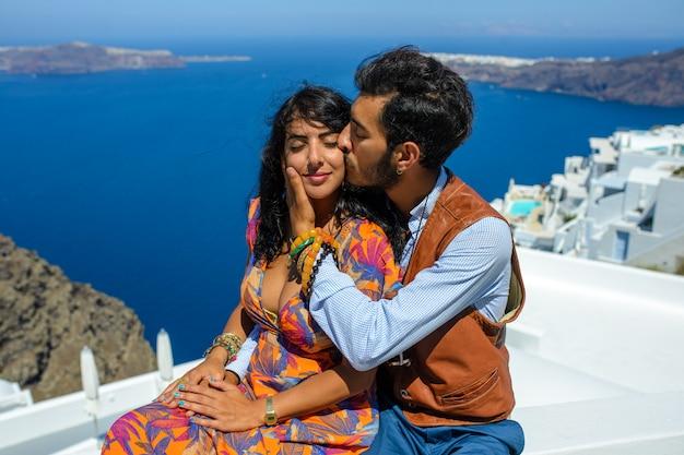 Een man en een vrouw kussen tegen de skaros-rots op het eiland santorini. het dorp imerovigli, hij is een etnische zigeuner. ze is een israëlische.