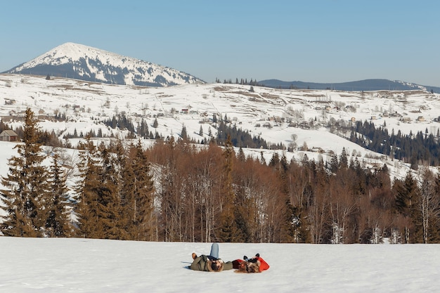 Een man en een vrouw liggen in de sneeuw