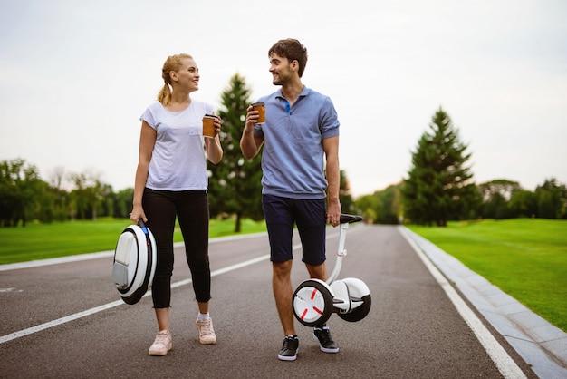 Een man en een vrouw lopen en houden koffie in hun handen.