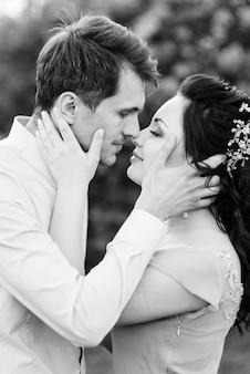 Een man en een vrouw lopen in de lentetuin van seringen voor de huwelijksceremonie