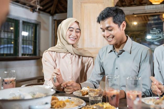 Een man en een vrouw met een hoofddoek lachen terwijl ze bijgerechten nemen als ze samen het vasten verbreken