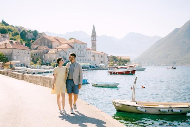 Een man en een vrouw met zonnebril lopen elkaar knuffelend op de pier bij de boten in het oude centrum van