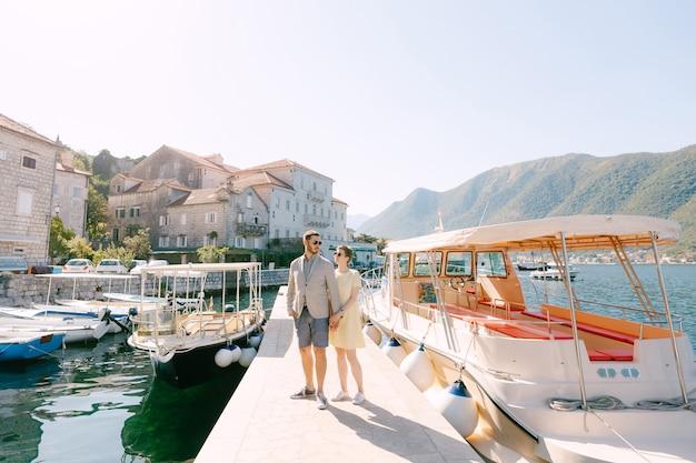 Een man en een vrouw met zonnebril staan elkaar te omhelzen op de pier bij de toeristenboten