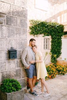 Een man en een vrouw omhelzen elkaar aan de muur van een mooi huis met een raam een liaanbloemen en een