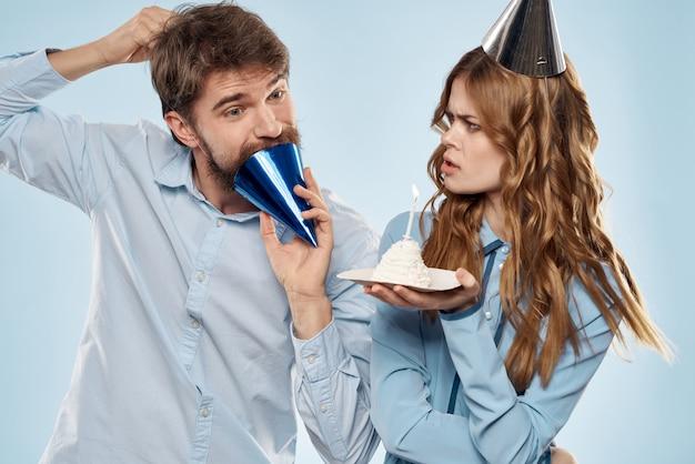 Een man en een vrouw op een verjaardag met een cupcake en een kaars in een feestelijke pet hebben plezier en vieren samen de vakantie