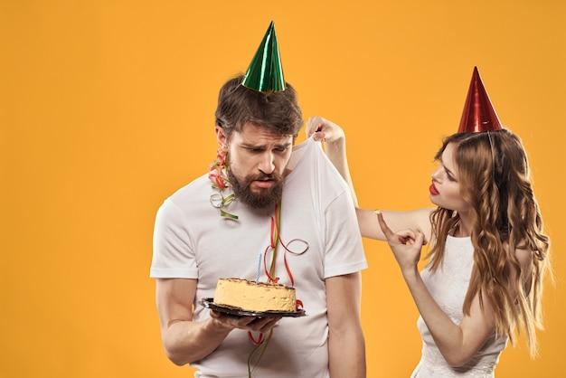 Een man en een vrouw op een verjaardag met een taart en een kaars hebben plezier