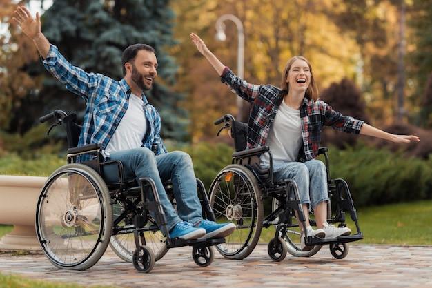 Een man en een vrouw op rolstoelen rijden door het park.