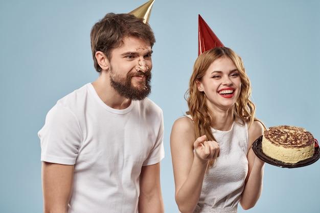 Een man en een vrouw op verjaardag met een taart en een kaars in feestelijke petten hebben plezier