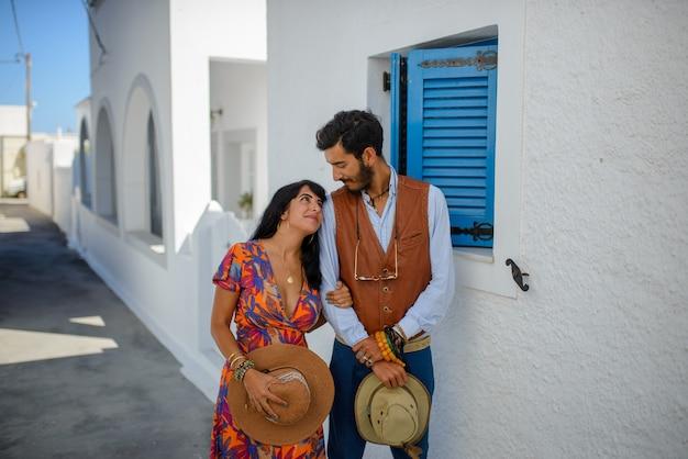 Een man en een vrouw poseren in de straten van imerovigli village, op het eiland santorini. hij is een etnische zigeuner. ze is een israëlische.