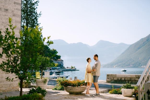 Een man en een vrouw staan in perast aan de oever van de baai van kotor omhelsd en kijken elkaar aan