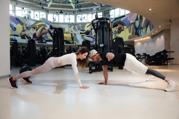 Een man en een vrouw trainen in de sportschool